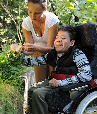 Eine Frau im Rollstuhl pfückt gemeinsam mit ihrer Betreuerin Blumen.