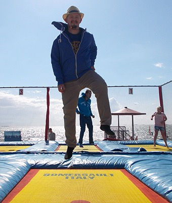 Mehrere Menschen hüpfen auf einem Trampolin. Im Hintergrund kann man das Meer sehen.