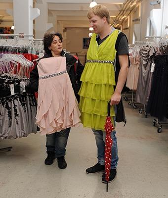 Eine Frau und ein Mann halten sich zum Spaß schicke Kleider vor den Körper.