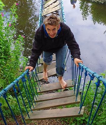Ein Junge klettert über eine Hängebrücke, die über einen Bach führt.