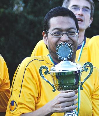 Ein Junge hält stolz seinen Pokal in der Hand.