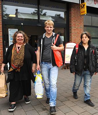 Drei Personen kommen aus dem Supermarkt. Sie tragen gemeinsam ihre Einkäufe.