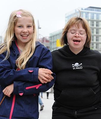 Zwei Mädchen halten einander fest und lächeln in die Kamera