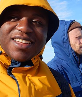 Zwei junge Männer mit Regenjacke und Kapuze stehen am Meer.
