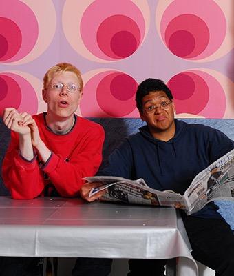 Zwei Jungs lesen Zeitung.