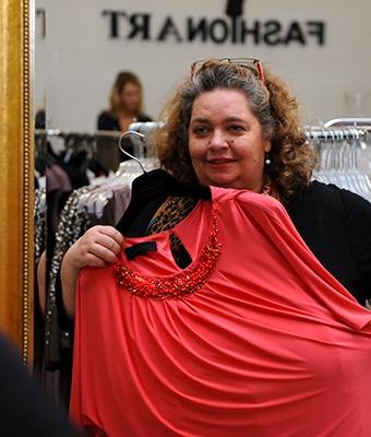 Eine Frau steht in einem Modegeschäft vor dem Spiegel. Sie hält sich ein Kleid vor den Körper und schaut, ob es ihr steht.