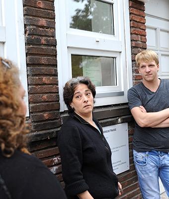Ein Mann und eine Frau lehnen an einer Hauswand und schauen einer weiteren Frau zu.
