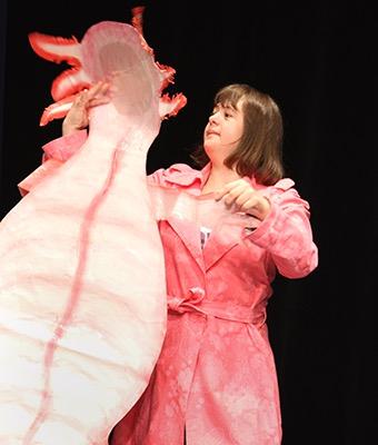 Ein Mädchen tanzt mit einem Fabelwesen auf einer Bühne.