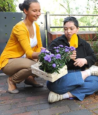 Zwei Mädchen kümmern sich um eine Pflanze.