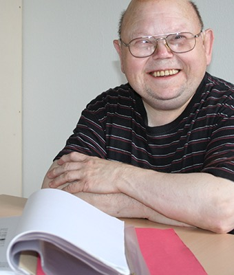 Ein Mann lächelt in die Kamera. Vor ihm auf einem Tisch liegt ein aufgeschlagener Ordner.