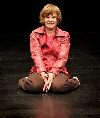Eine junge Schauspielerin kniet auf einer Bühne und grinst in die Kamera.