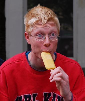 Ein junger Mann genießt ein Eis am Stiel.