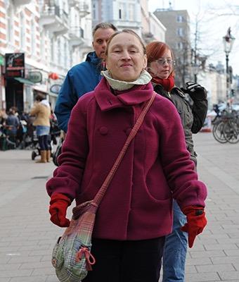 Eine Gruppe von drei Personen steht in der Fußgängerzone. Sie schauen herausfordernd in die Kamera.