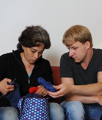 Eine Frau und ein Mann sortieren Wolle in eine Tasche.