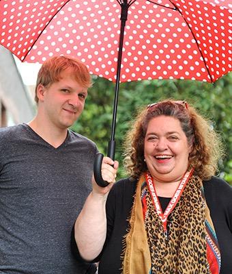 Ein Mann und eine Frau stehen gemeinsam unter einem Sonnenschirm.