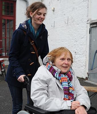 Eine Rollstuhlfahrerin und ihre Begleiterin sind auf dem Weg zu einer Kulturveranstaltung. Beide sehen glücklich aus.