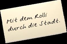 """Auf einem Zettel steht: """"Mit dem Rolli durch die Stadt."""""""