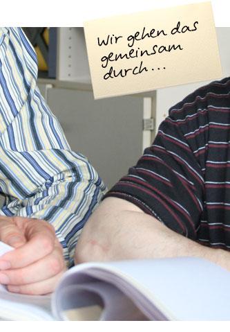"""Detailaufnahme von einer Hand, die auf einer Akte liegt. Auf einem Zettel oben im Bild steht: """"Wir gehen das gemeinsam durch ..."""""""