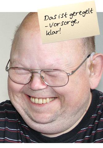 """Portrait eines Mannes. Auf einem Zettel oben im Bild steht: """"Das ist geregelt - Vorsorge, klar!"""""""