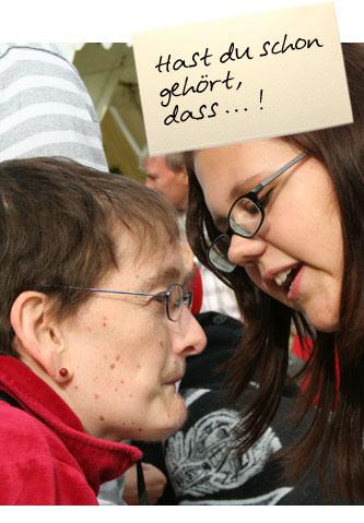 """Zwei Frauen sind ins Gespräch vertieft. Auf einem Zettel oben im Bild steht: """"Hast du schon gehört, dass ..."""""""