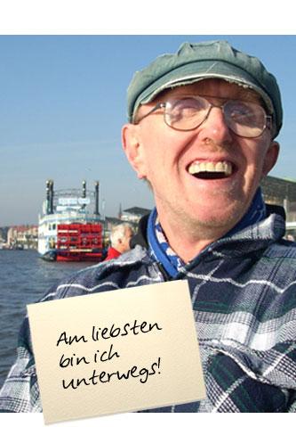 """Ein Mann mit Schiffermütze lacht in die Kamera. Im Hintergrund sieht man den Hamburger Hafen. Auf einem Zettel unten im Bild steht: """"Am liebsten bin ich unterwegs"""""""